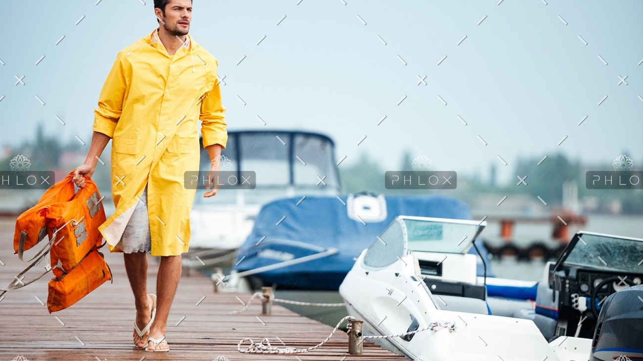 demo-attachment-32-sailor-in-yellow-cloak-at-the-pier-holding-life-PX7M94D